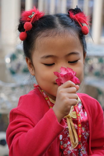Portrait of cute girl holding red flowers