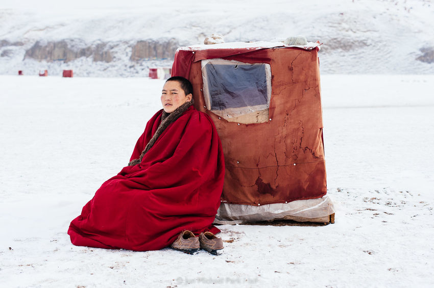 A Tibetan nun is sitting in front of her study box in a sub-zero temperature at Yarchen Gar. The boxes are humbly made of wooden plates and tarp, and barely shield the occupant from winter cold and wind. 03.03.10. A Journey To Nirvana China Documentary Documentary Photography Jun Michael Park Photojournalism Portrait Reportage Sichuan Snow Tibet Tibetan Buddhism Travel Travel Photography Winter Yarchen Gar