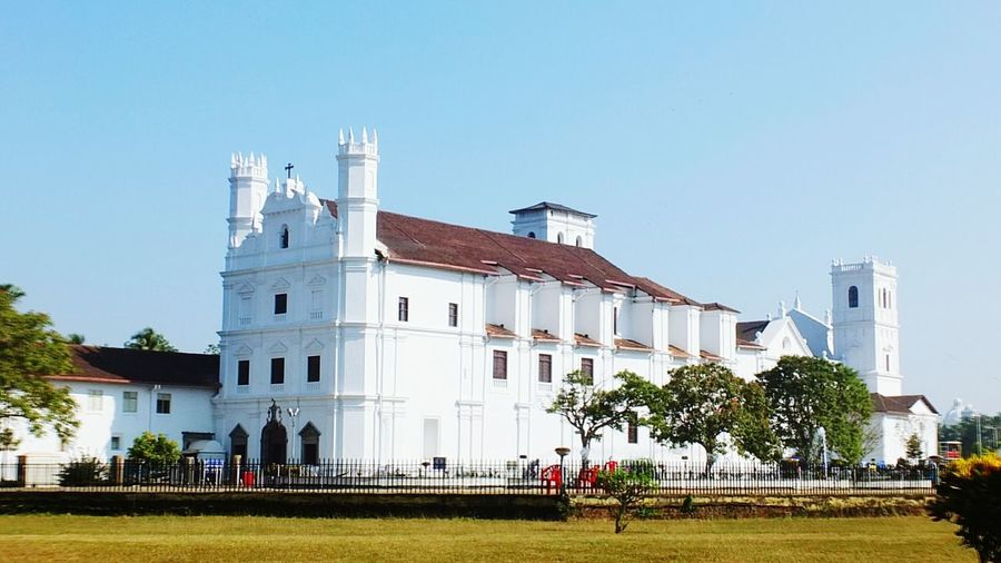 India Oldgoa Goa GOGOA Goatourism Church Architecture Oldchurch Historic Site Tree City Clear Sky Sky Architecture Building Exterior Grass Built Structure Historic Cathedral Cityscape