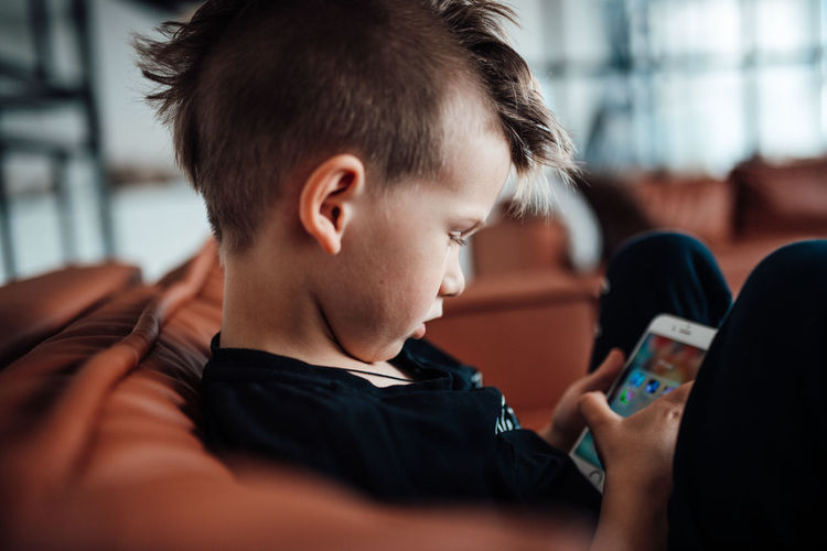 Side view of boy using smart phone while sitting on sofa at home