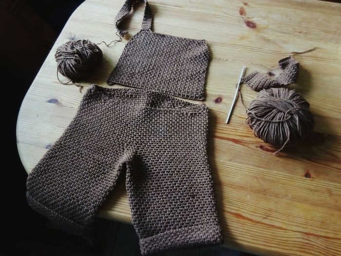 High Angle View Of Incomplete Sweater With Crochet Hook And Wool On Table
