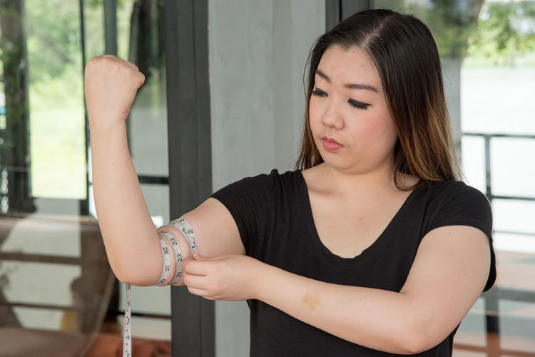 Young woman measuring biceps with tape
