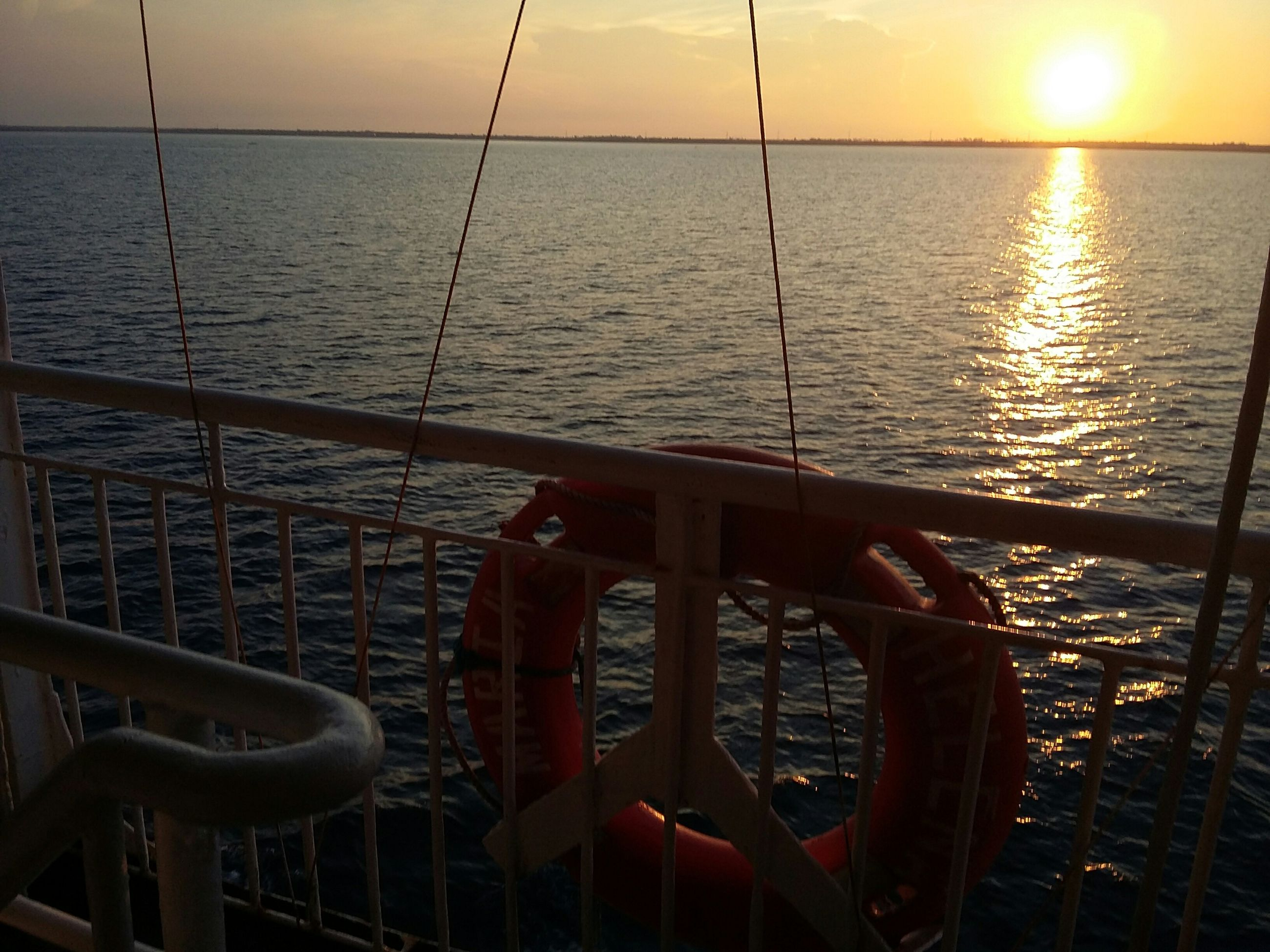 water, sea, sunset, nautical vessel, transportation, mode of transport, boat, horizon over water, tranquility, sky, scenics, tranquil scene, sun, nature, rippled, beauty in nature, sunlight, reflection, orange color, travel