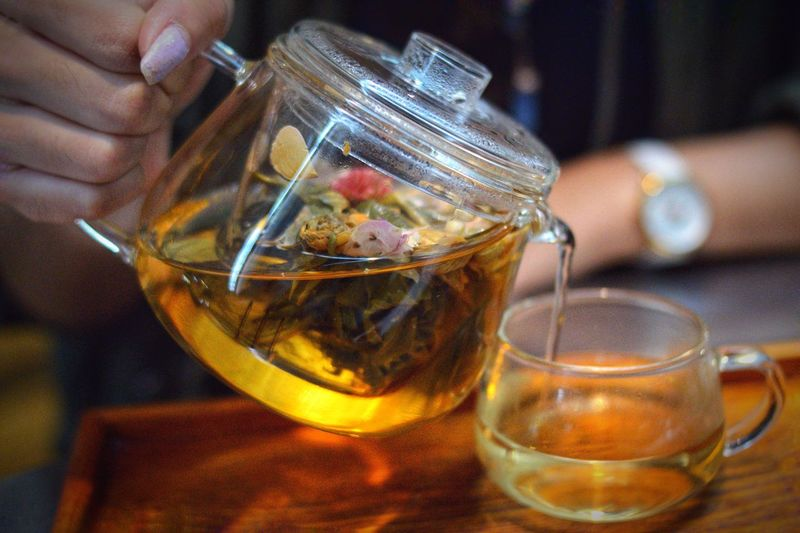 Cropped hand of woman pouring herbal tea in cup