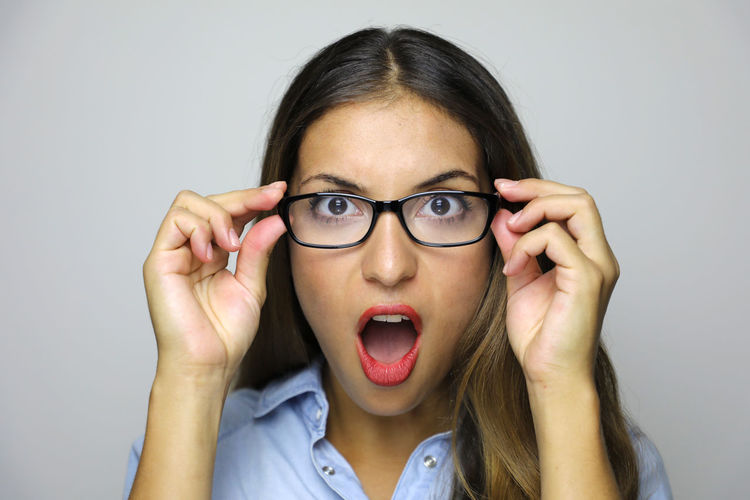Close-Up Portrait Of Shocked Young Woman Wearing Eyeglasses Against Gray Background
