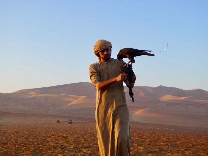 Early in the morning Rub Al Khali Falconer Falcon Sand Real People Desert One Person Clear Sky Nature One Animal Sand Dune