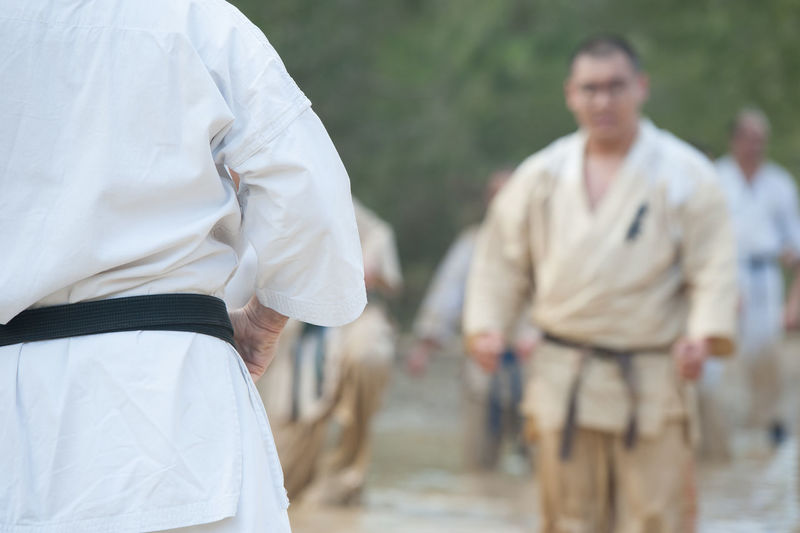 Midsection of man teaching karate to students