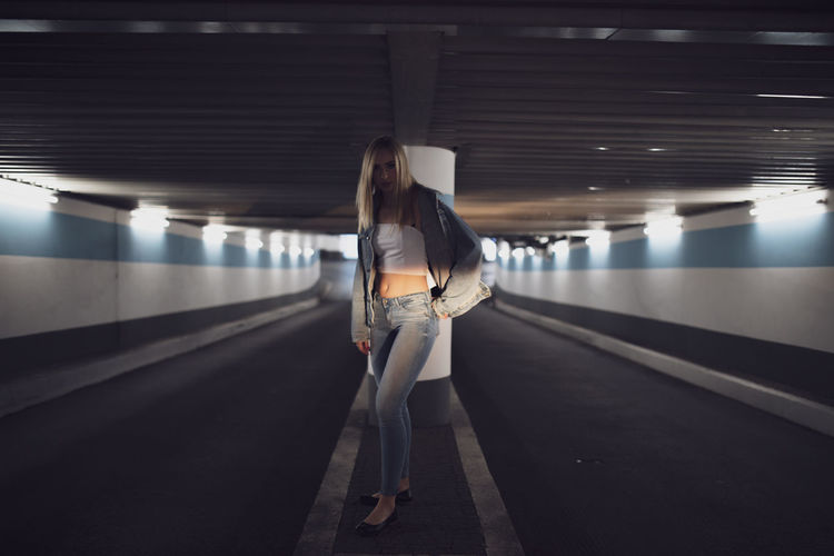 Portrait of serious woman standing under illuminated tunnel