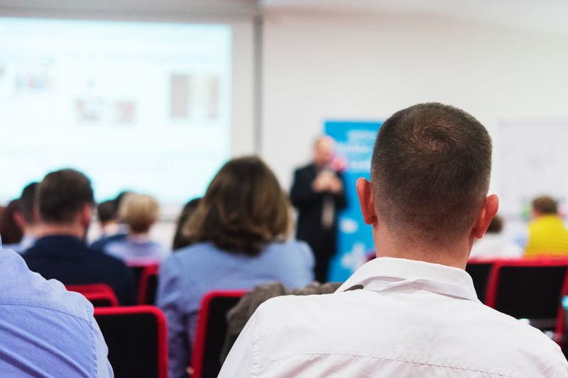 Rear view of man sitting at seminar