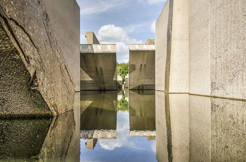 Large concrete hydrolic test facility, no longer in use, reflecting in the surrounding canal
