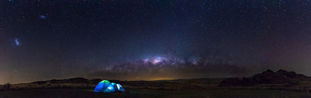 Scenic view of landscape against star field at night