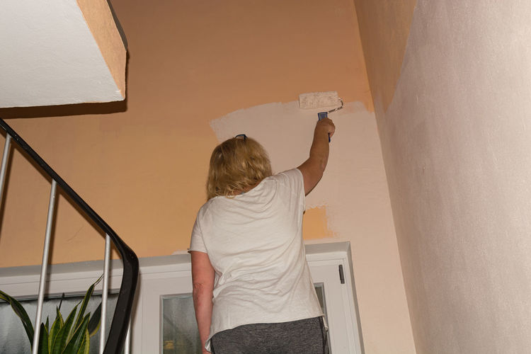 Rear view of woman standing against wall at home