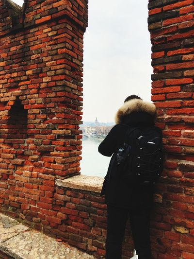 City Wall Day Brick Rear View Sky Real People Architecture Built Structure Building Exterior Brick Wall One Person Standing Building Lifestyles Leisure Activity Wall - Building Feature Women Adult Clothing Outdoors Stone Wall Warm Clothing Hood - Clothing Hairstyle Wall Brick Wall Architecture Standing Adult