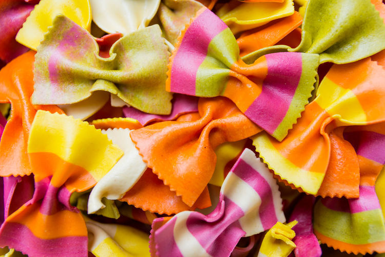 Traditional handmade italian farfalle pastas close up colored background Appetizing  Background Colored Cooking Extreme Close-up Farfalla Farfalle Food Food And Drink Freshness Green Italia Italian Italy Macro Multi Colored Pasta Pastas Penne Pink Spaghetti Tasty Vibrant Color Yellow Yummy