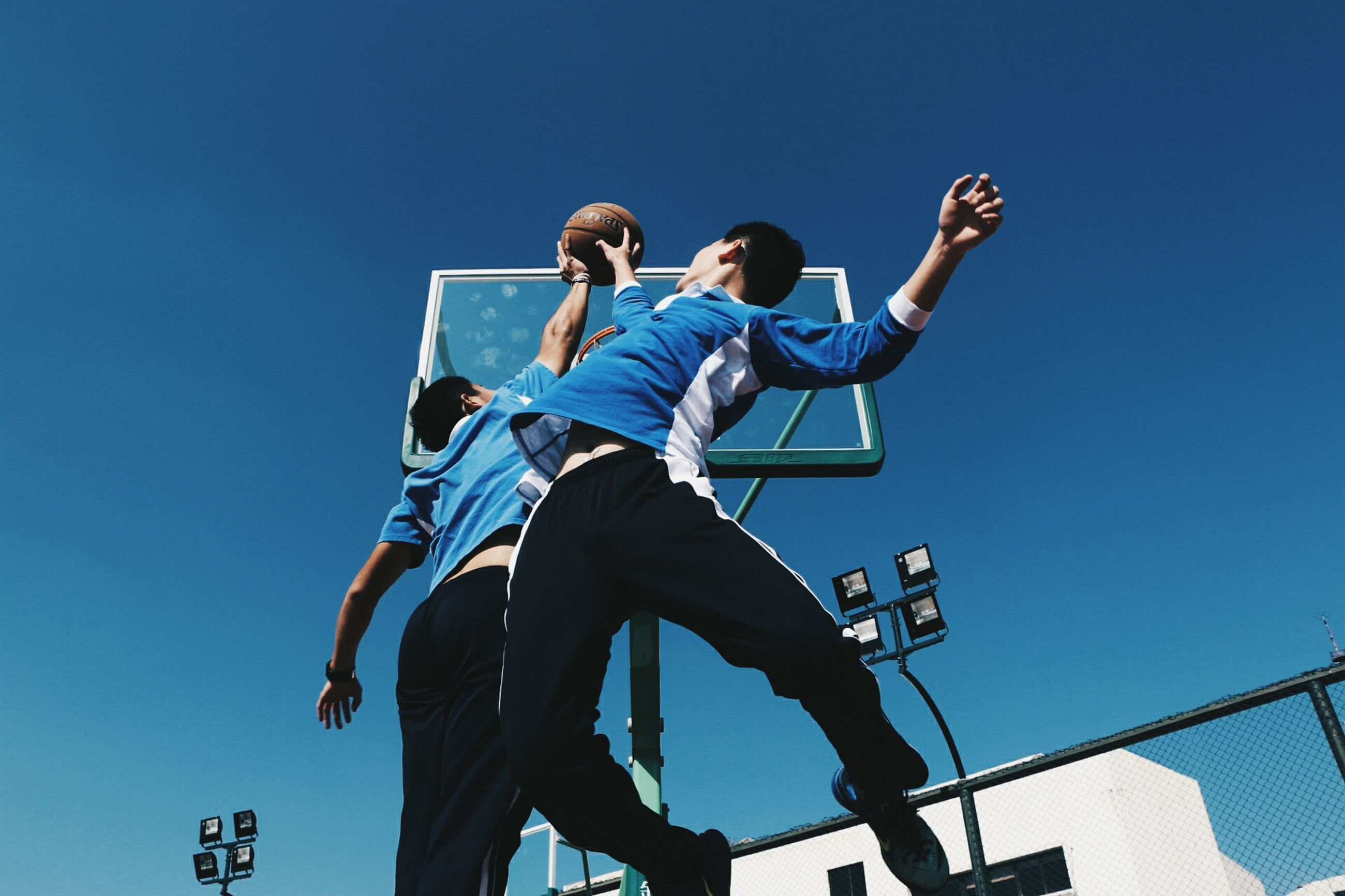low angle view, blue, jumping, leisure activity, friendship, sport, activity, full length, men, fun, two people, motion, lifestyles, sky, arts culture and entertainment, women, outdoors, stunt, people, real people, togetherness, human body part, young adult, athlete, sportsman, competition, cheerful, adult, day, adults only, sports event, golfer, motorsport