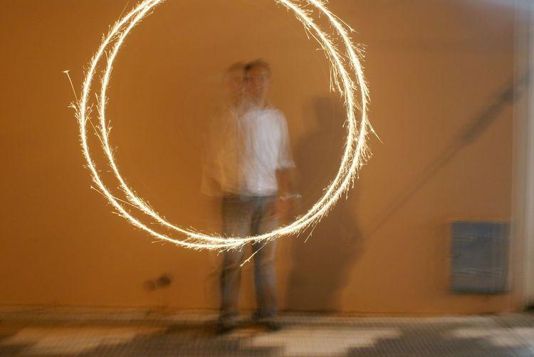 Light Painting Against Defocused Man At Night