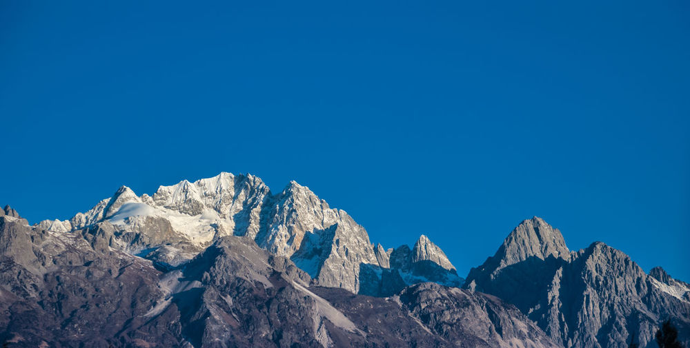 Low angle view of rocky mountains against blue sky