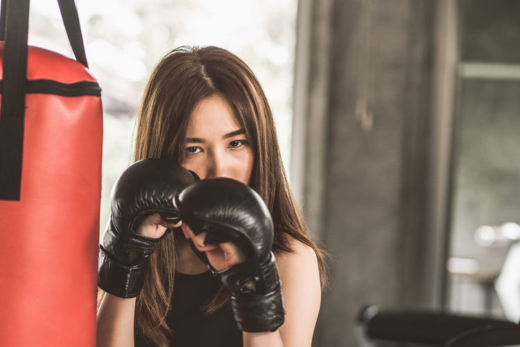 Portrait Of Confident Young Woman Punching Bag In Gym