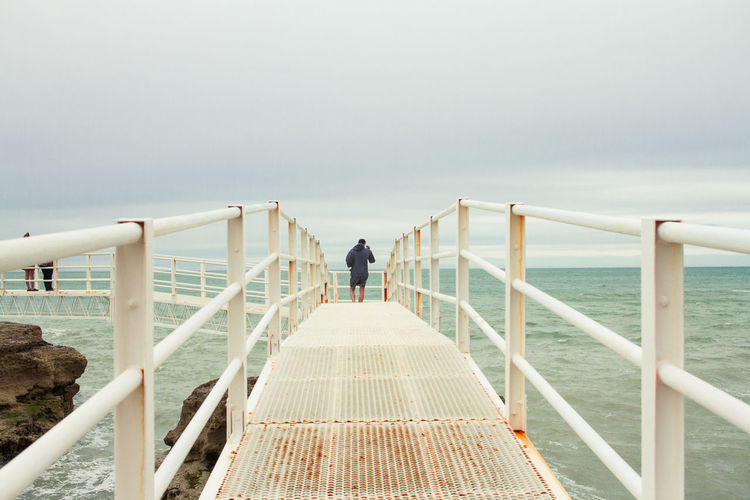 Rear view of man walking on pier over sea against cloudy sky