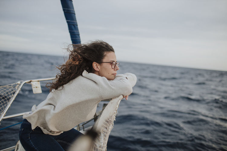 Young woman sitting on boat in sea against sky