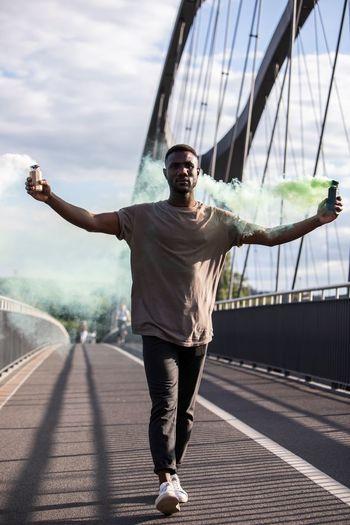 Full length of man holding distress flare walking on footbridge against sky