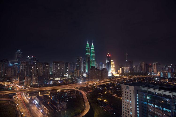 Illuminated petronas towers in city against sky at night