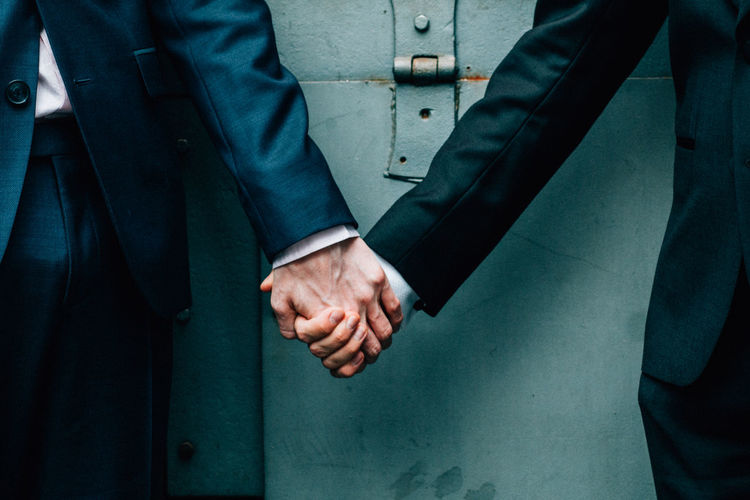 Midsection of homosexual couple holding hands against door during wedding