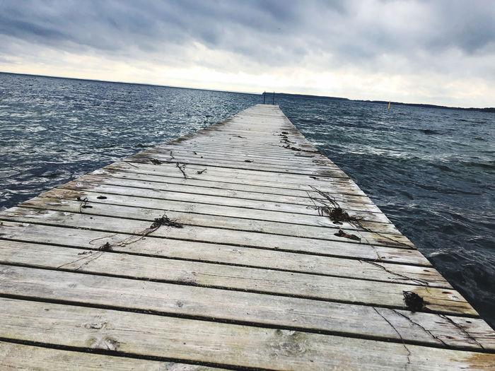 Shadow of pier on sea against sky