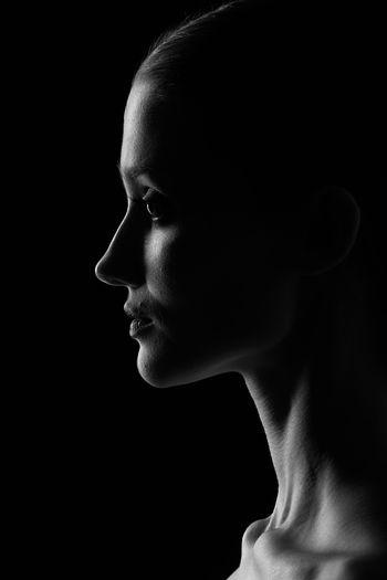 Portrait of boy looking away against black background