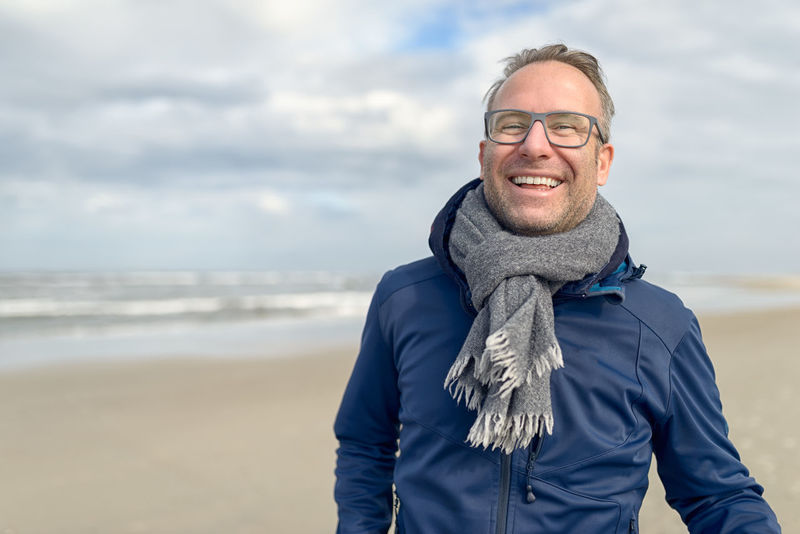Happy smiling middle-aged man walking on the beach Autumn Beach Fall Glasses Happy Looking At Camera Male Man Middle-aged North Sea Sea Smiling Walking Windy