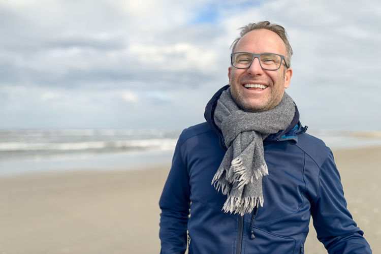 Happy middle-aged man on an autumn beach Adult Autumn Beach Coast Eyeglasses  Face Fall Glasses Happy Laughing Looking At Camera Middle-aged North Sea One Person Portrait Scarf Smiling Standing Tourism Travel Upper Body Walking