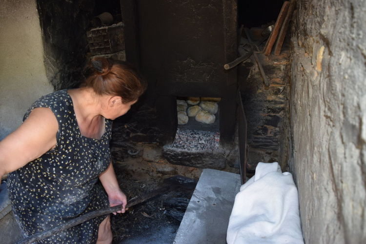 High angle view of woman positioning breads in wood burning stove