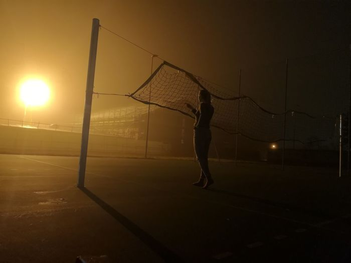 Full length of silhouette woman playing soccer against sky during sunset