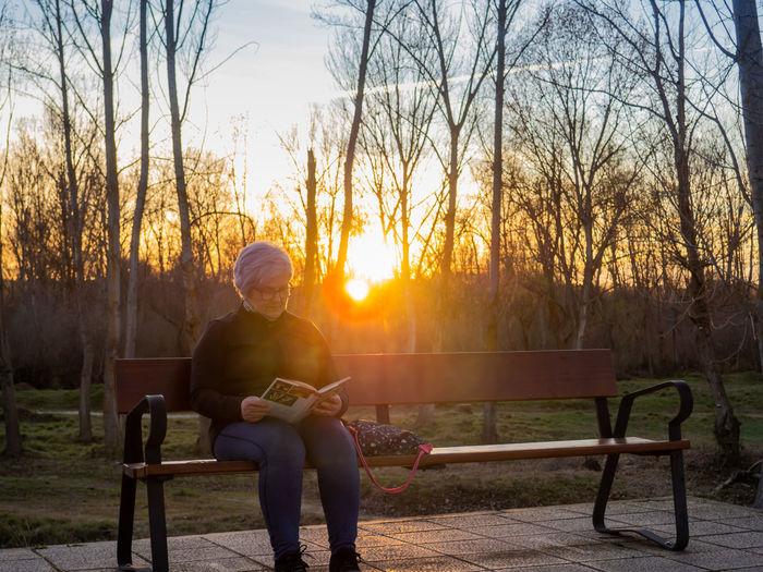 Man sitting on bench at park during sunset
