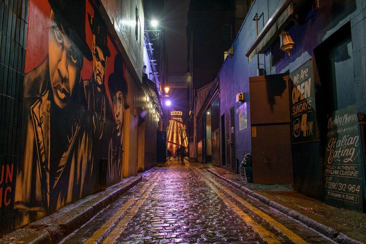 Street amidst illuminated city at night