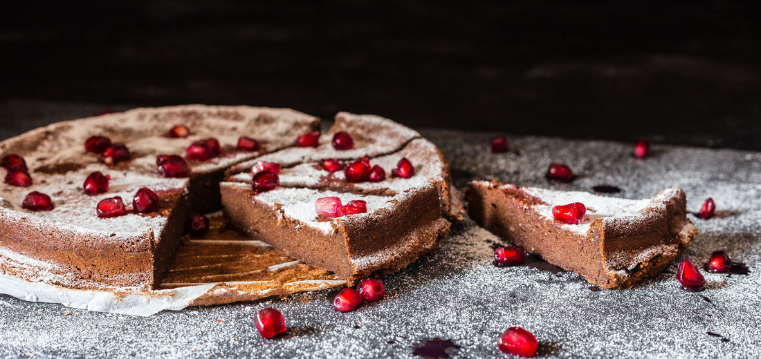 Close-up of pomegranate seeds on chocolate cake