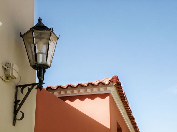 Low angle view of gas light mounted on building against clear sky