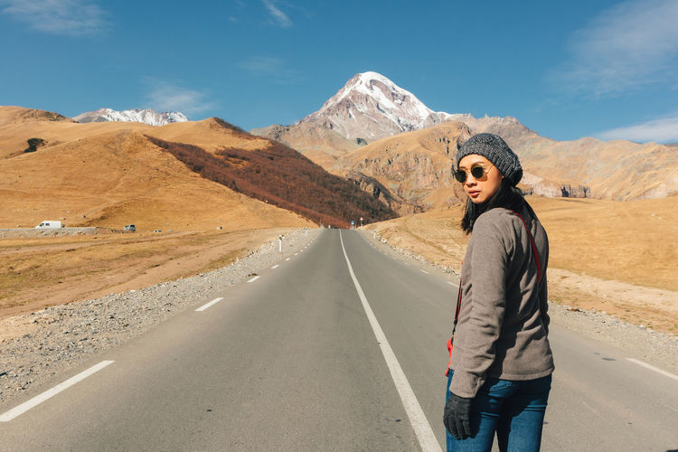 Portrait of young woman standing on road against mountain