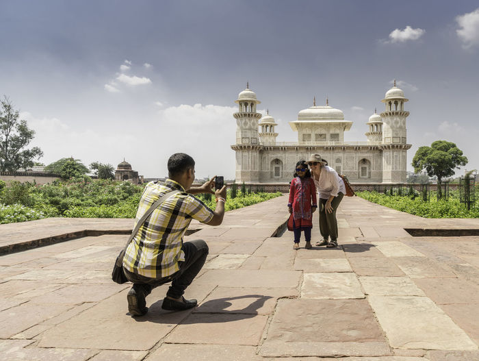 An Indian visitor asks a young western woman to pose for a photograph with his daughter at the Tomb of Itimad-ud-Daulah also known as the 'Baby Taj' India Indian Indian Culture  Indianstories Indianphotography Travel Photography Travelphotography Architecture Real People Built Structure Building Exterior Men Sky Nature History Lifestyles The Past People Tourism Travel Full Length Rear View Travel Destinations Day Two People Adult Women Outdoors