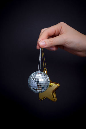 Christmas and New Year's Eve Christmas Star Black Background Close-up Decoration Gold Colored Hanging Human Body Part Human Hand Indoors  Mirror Ball New Years Eve One Person Ornaments Studio Shot