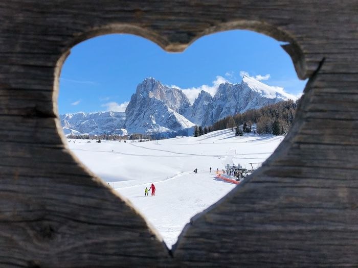 Scenic view of snowcapped mountains seen through heart shape wooden fence