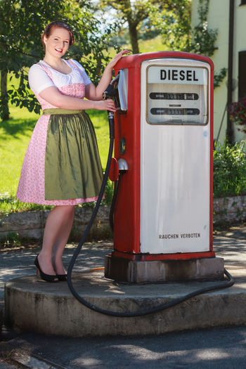 Portrait of woman in dirndl standing at gas station