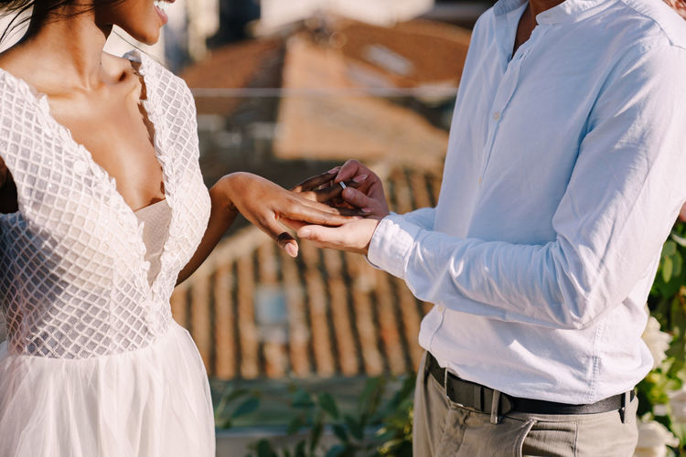 Midsection of man putting ring in womans hand