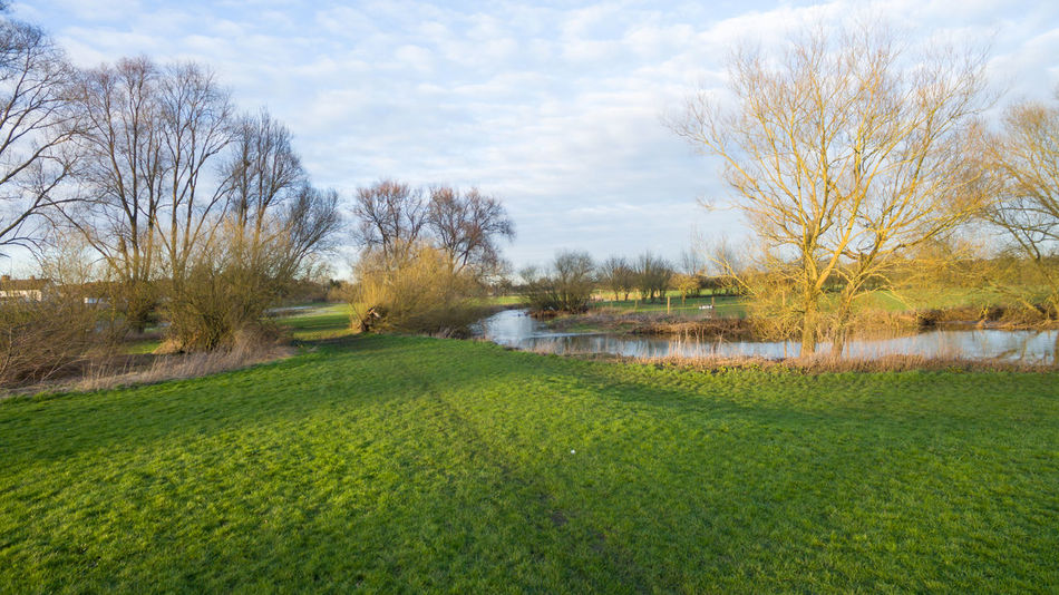 Aerial view over a lake & river at sunset in winter in the countryside around Leicester, UK. Aerial Photography Aerial View Bushes Cloudy Sky 💙 Daytime Dronephotography Green Grass 🌱 Lake View Outdoors Outside River Sunset Trees