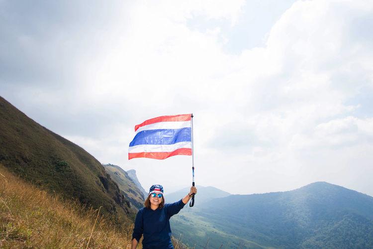 Happy woman waving thai flag on mountain against cloudy sky