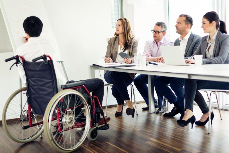 Accessibility Business Business Person Businessman Businesswoman Career Communication Cooperation Corporate Business Disability  Discussing Discussion Full Length Indoors  Integration Meeting Meeting Men Occupation Office Sitting Teamwork Wheelchair Women Working