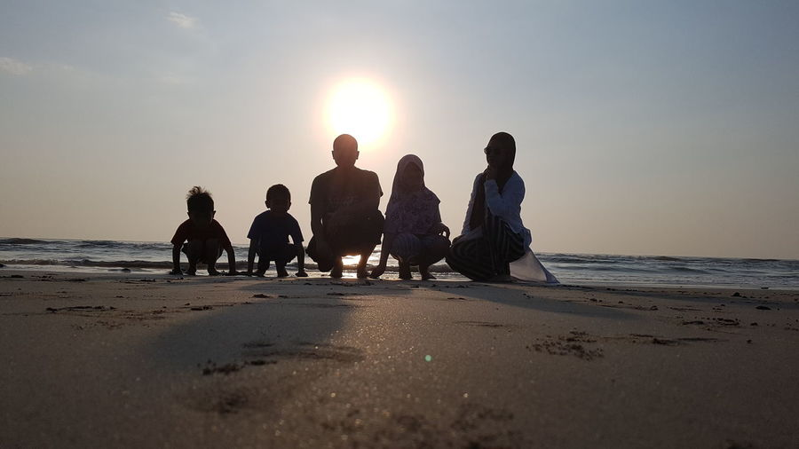 Surface level shot of family crouching on shore at beach against sky during sunset
