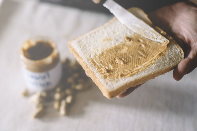 Close-Up Of Person Applying Peanut Butter On Bread On Table