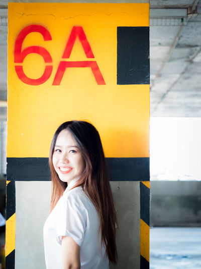 Portrait of smiling young woman standing against number and alphabet on yellow wall