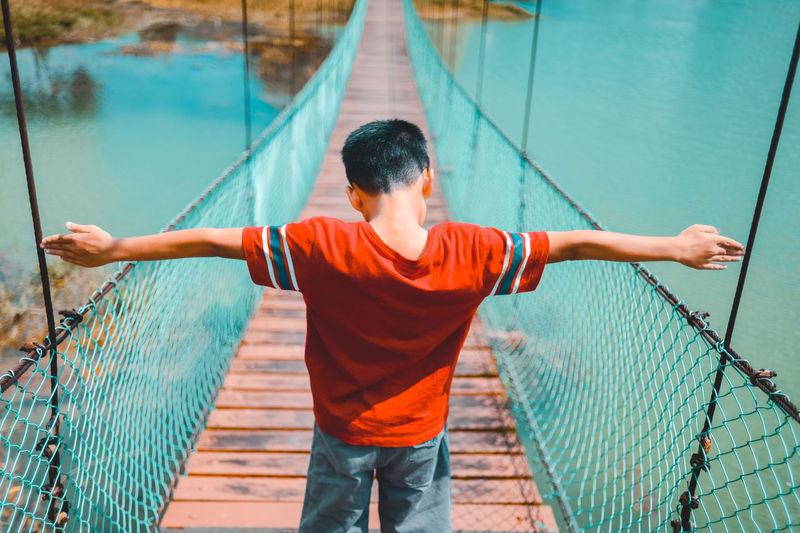 Rear view of boy with arms outstretched standing on footbridge